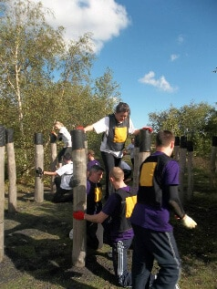 Sleeping Giant Media at KM Assault Course Challenge using teamwork to climb from one pole to another